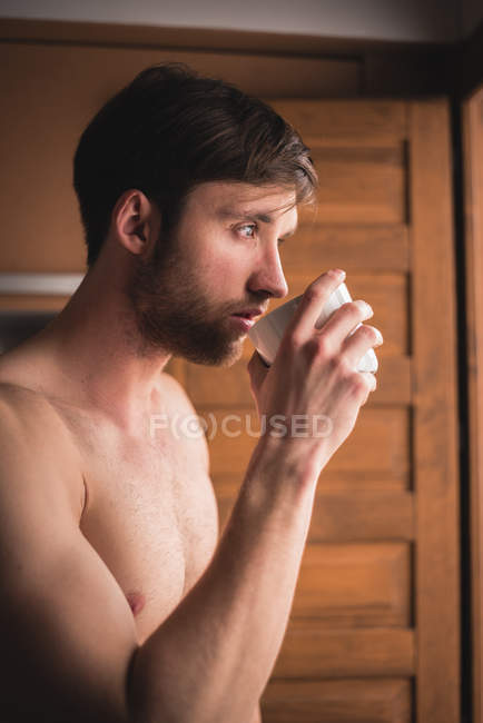 Young shirtless man drinking coffee — Stock Photo
