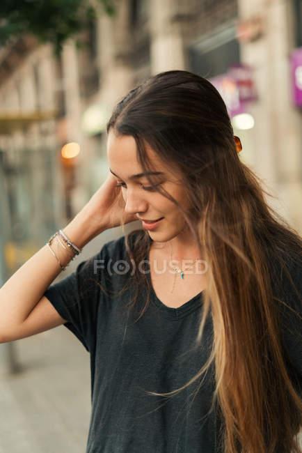 Portrait of brunette girl posing with hand in hair at street scene — Stock Photo