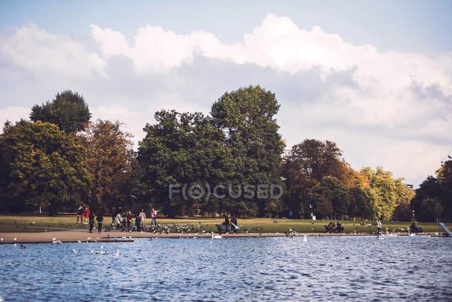 Paisaje de lago con gente descansando - foto de stock