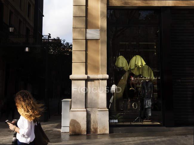 Вид збоку жіночого пішохідної проходження одягу магазин на розі. — стокове фото