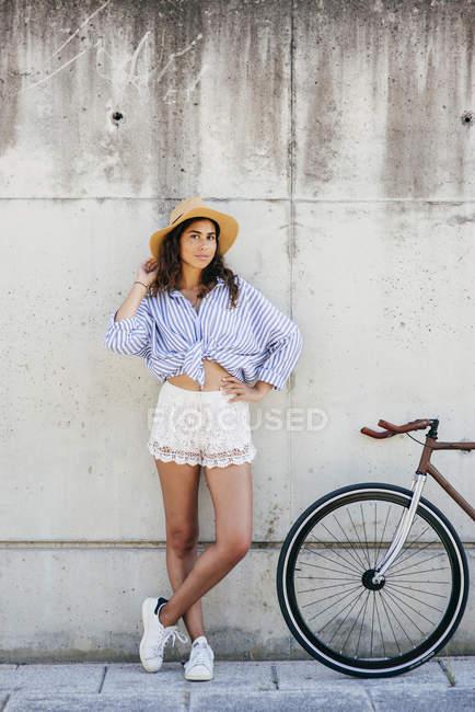 Девушка позирует возле велосипеда — стоковое фото
