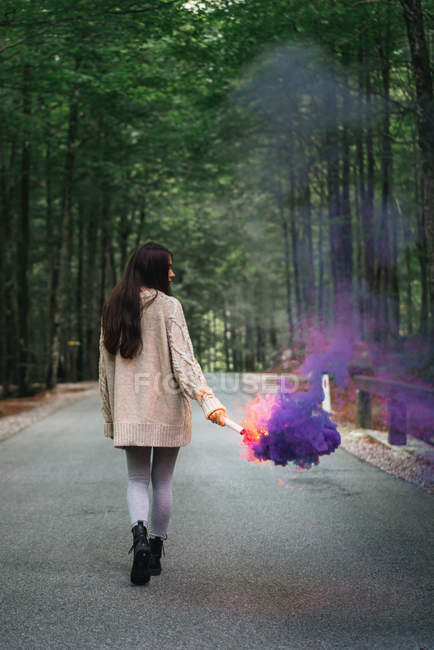 Girl walking with smoke torch at forest road — Stock Photo