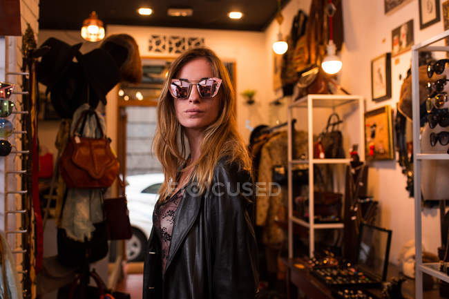 Young girl in sunglasses posing on background of clothing room. — Stock Photo