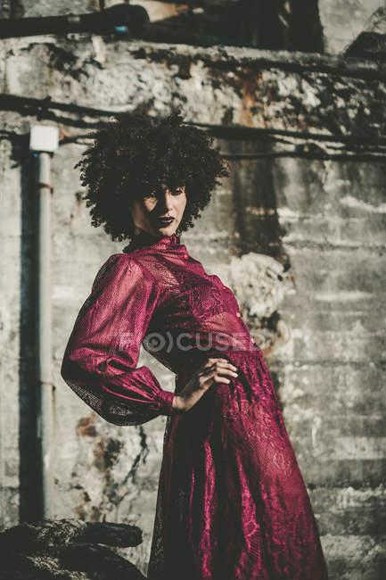 Fille à la mode posant en robe transparente pourpre avec des bras à la taille — Photo de stock