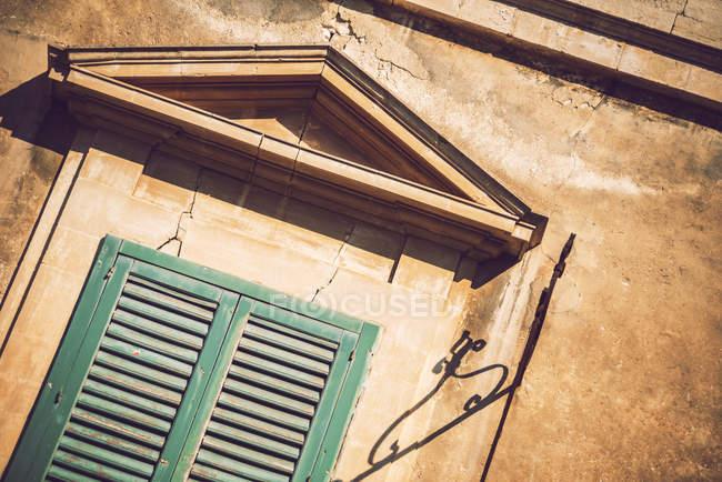 Facciata edificio illuminato dal sole con persiane chiuse — Foto stock