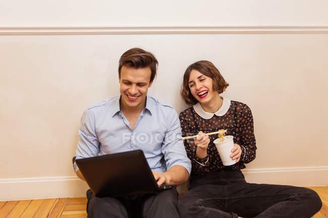 Zwei junge Freunde fröhlich auf Boden sitzend und mit Blick auf Laptop mit snack.s — Stockfoto
