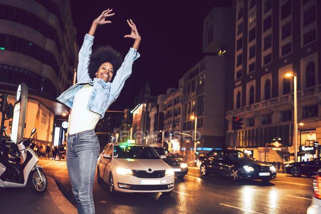 Красива молода чорна жінка стрибки на вулиці вночі — стокове фото