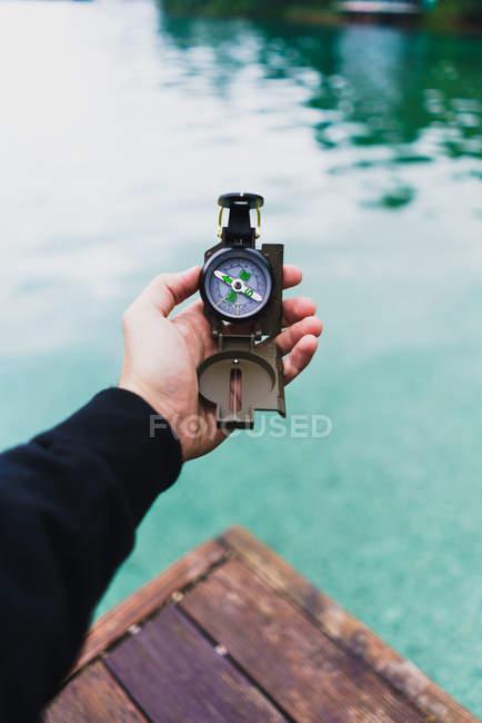 Bussola di holding mano maschio raccolto sopra acqua — Foto stock