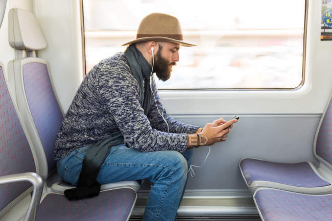 Side view of bearded man listening music with earphones and surfing smartphone while riding train. — Stock Photo