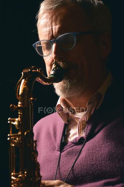 Зрелый мужчина в очках, играет саксофон с глаза закрыты на черном фоне — стоковое фото