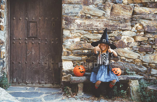 Девушка в костюме ведьмы сидит на скамейке — стоковое фото