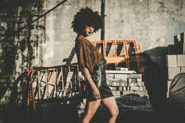 Young woman with afro wearing leather skirt posing at construction plant — Stock Photo