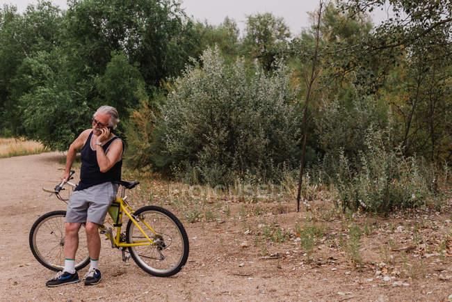 Портрет пожилого человека, опирающегося на велосипед и разговаривающего по смартфону в парке — стоковое фото
