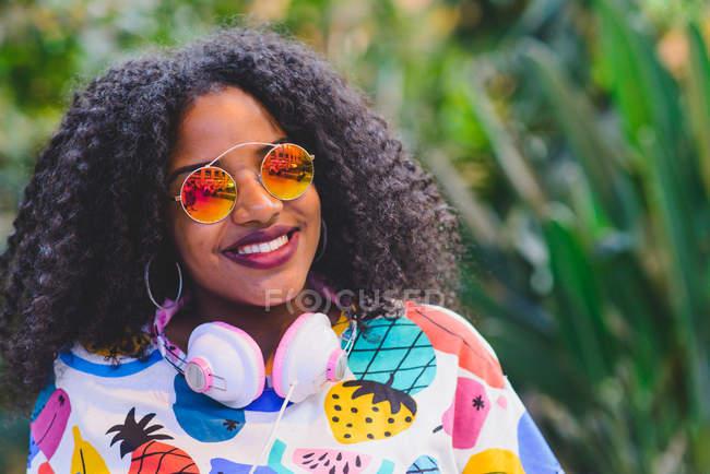 Portrait of smiling girl in mirrored sunglasses wearing headphones around her neck — Stock Photo