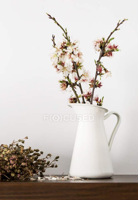 Fresh cut blooming sprigs in vase on shelf — Stock Photo