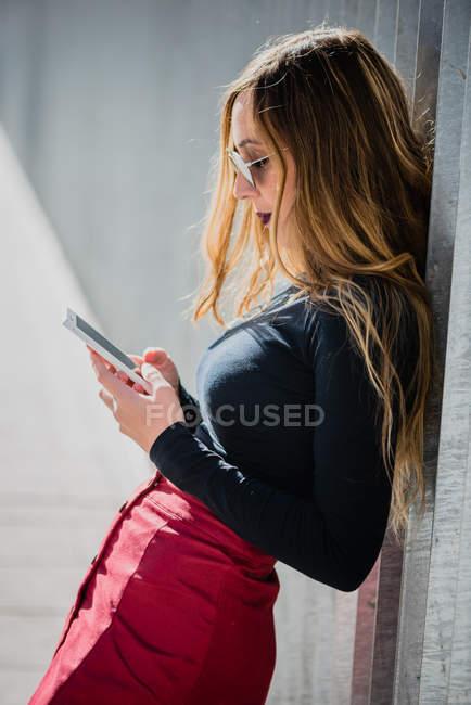 Девушка в солнечных очках с помощью смартфона — стоковое фото