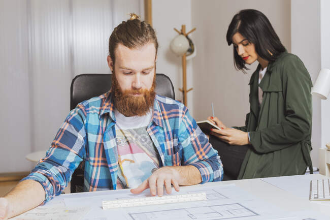 Portrait of beared man working with blueprint while female colleague writing in notepad. — Stock Photo