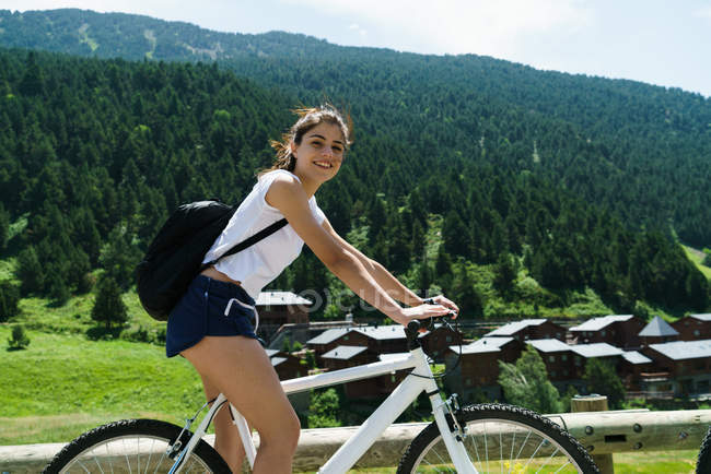 Girl on bicycle looking at camera over mountain slope — Stock Photo