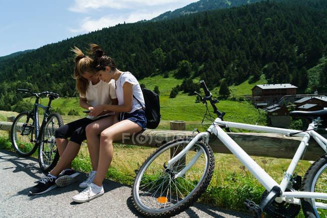 Девушки сидят с велосипедами и используют смартфон — стоковое фото