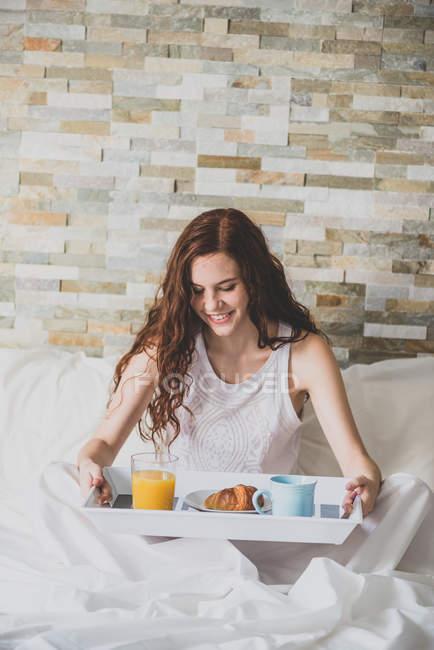 Девушка держит поднос с завтраком в постели — стоковое фото