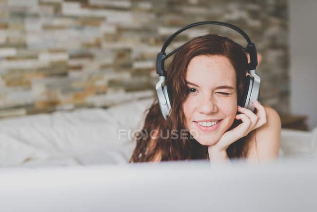 Femme avec écouteurs plissant à la caméra — Photo de stock