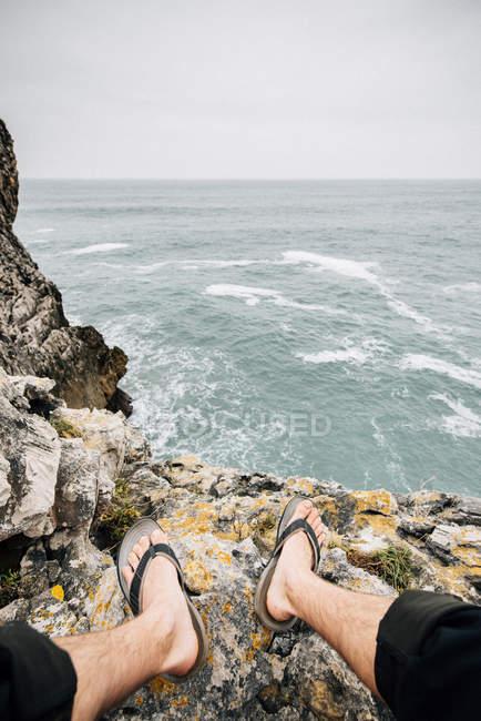 Обітнути Босий людина сидить на скелястому узбережжі лінія — стокове фото