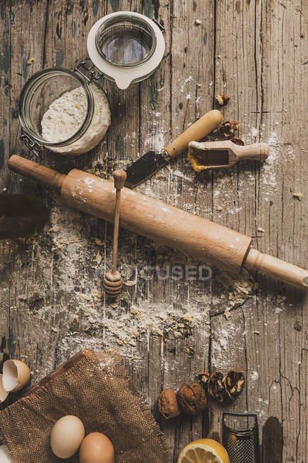 Draufsicht der Backzutaten und Nudelholz auf rustikalen Holztisch — Stockfoto