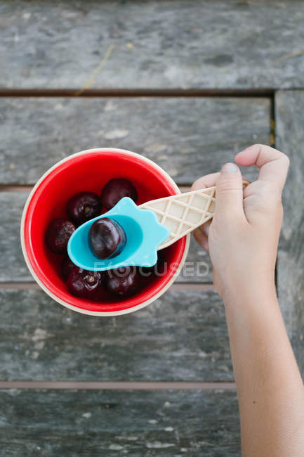 Hand of little girl taking cherry with spoon from bowl — Stock Photo