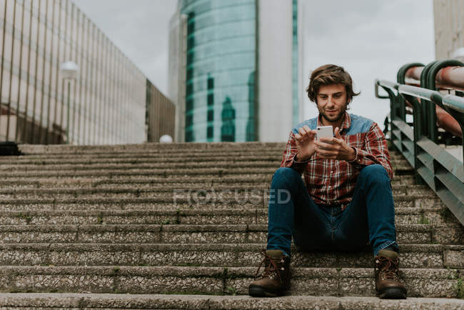 Portrait of smiling bearded man in casual clothes sitting on street steps and using phone — Stock Photo
