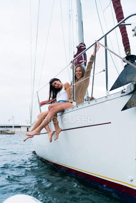 Portrait of happy girls posing on edge of yacht deck and looking at camera — Stock Photo