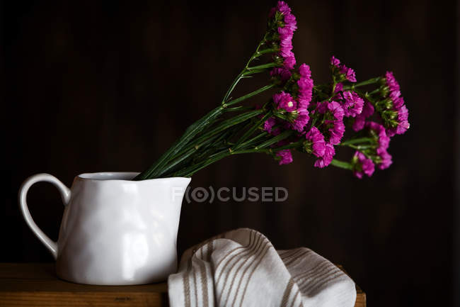 Fresh purple carnations in mug on dark background with kitchen towel — Stock Photo