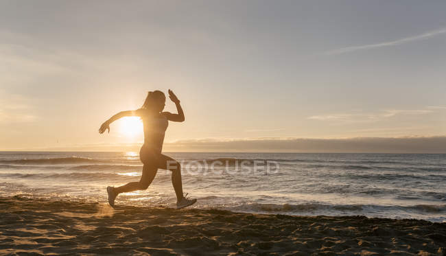 Fitness womans silhouette running on beach — Stock Photo