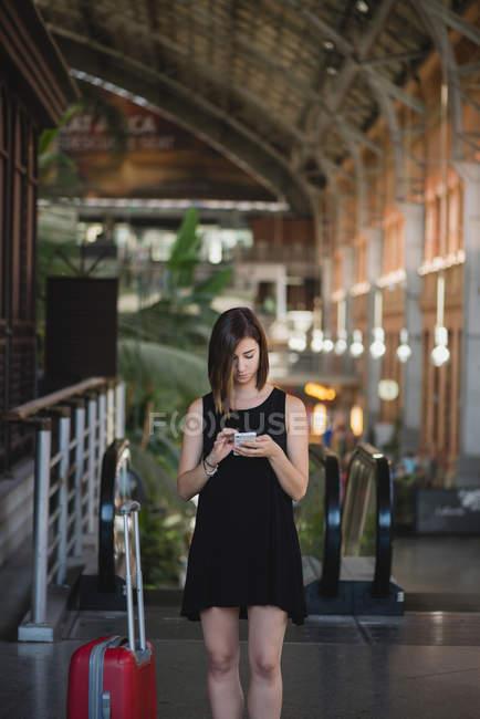 Retrato de niña con maleta roja de pie cerca de la escalera mecánica y el uso de teléfono inteligente - foto de stock