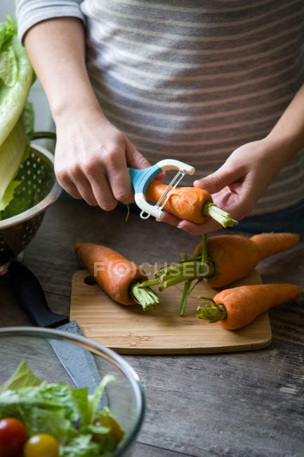 Midsection of woman peeling carrot with vegetable peeler — Stock Photo