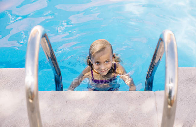 Blonde kid in swimming pool by ladder — Stock Photo