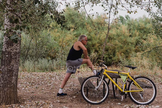 Vue latérale de l'homme âgé étirant les jambes dans le parc près du vélo — Photo de stock