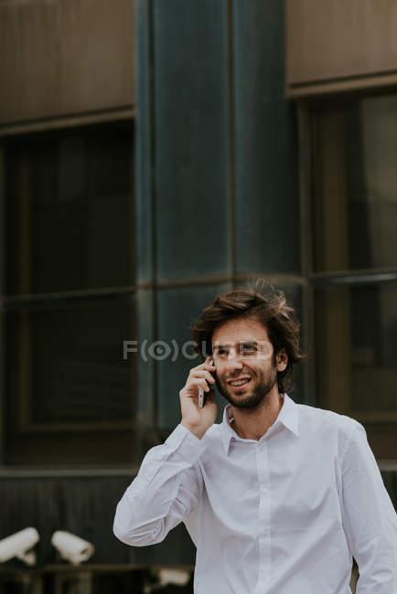 Портрет уверенного бизнесмена в белой рубашке, разговаривающего на смартфоне на городской сцене — стоковое фото