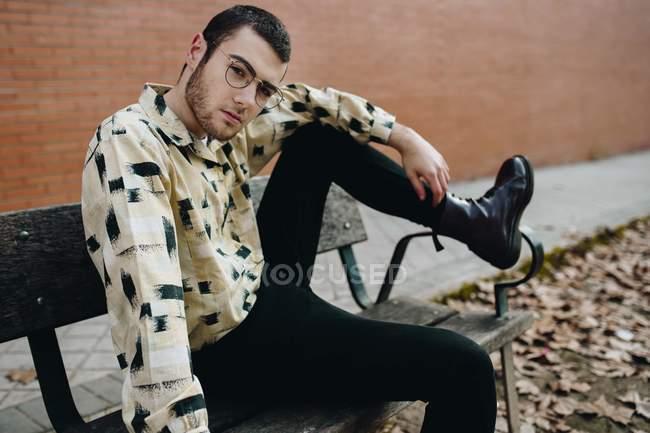 Porträt des Mannes in Brillen sitzen auf Bank mit Bein am Handlauf und Blick in die Kamera — Stockfoto