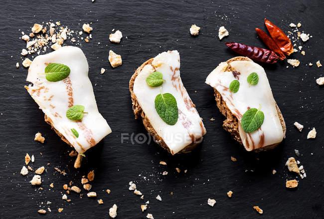 Sanduíches com bacon salobra e folhas de hortelã na ardósia — Fotografia de Stock