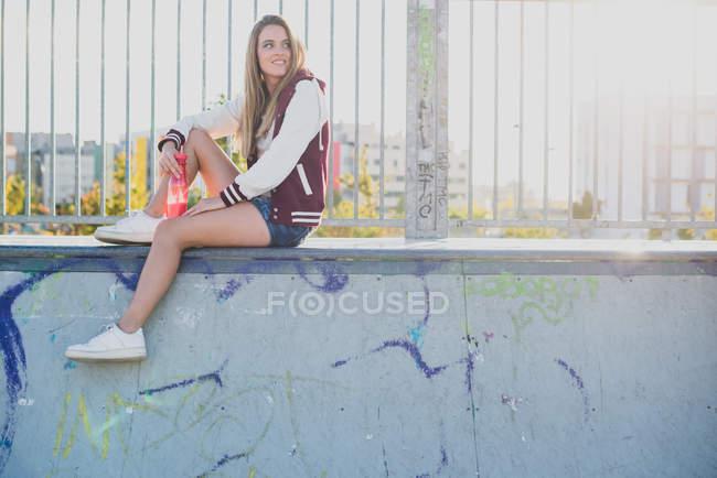 Vue latérale de jolie fille assise sur une clôture avec bouteille et regardant de côté — Photo de stock