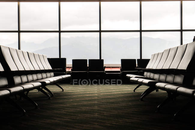 Empty seats in airport lounges against big windows. — Stock Photo