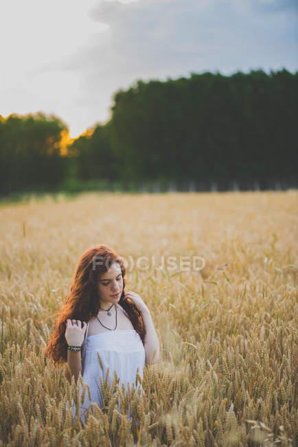 Портрет рыжеволосой девушки в белом платье, позирующей на ржаном поле на закате — стоковое фото