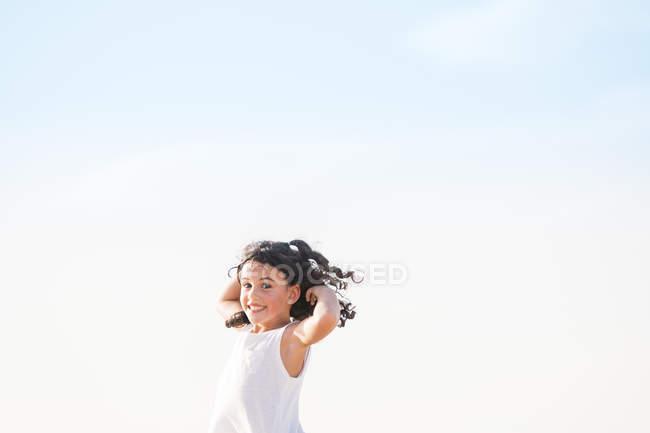 Portrait d'enfant brune joyeux avec sourire de dents et cheveux volants contre le ciel bleu . — Photo de stock