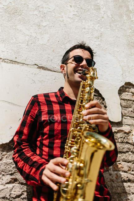 Mann lehnt sich an Wand und spielt Saxofon — Stockfoto