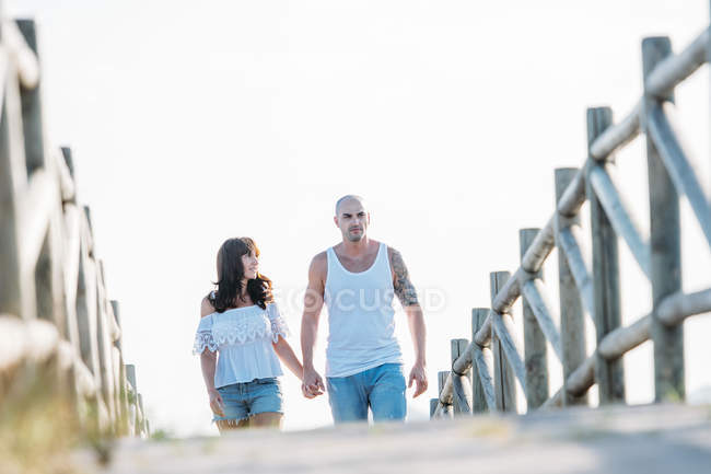 Couple holding hands and walking on wooden boardwalk — Stock Photo