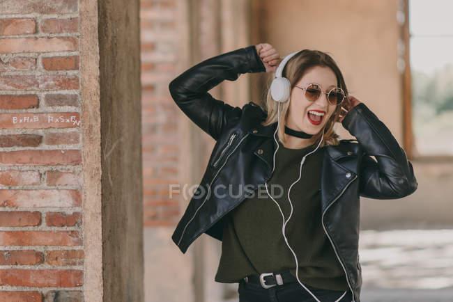 Fille dans les écouteurs, posant avec les bras levés pliés — Photo de stock