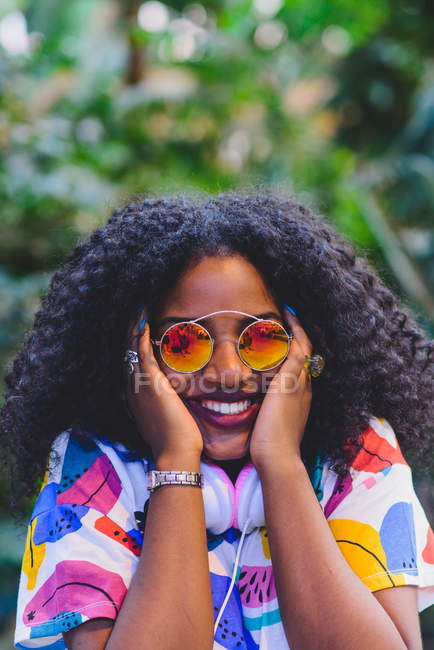 Portrait of cheerful woman with afro hairstyle in mirrored sunglasses with hands on cheeks. — Stock Photo