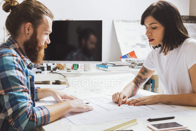 Man and woman discussing sketches — Stock Photo