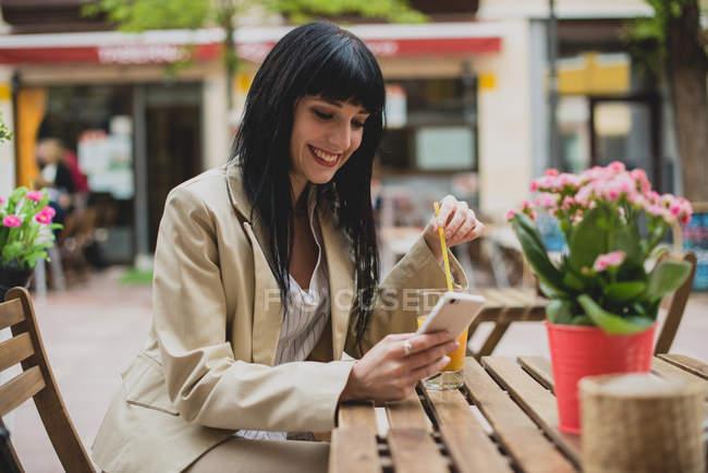 Mujer usando smartphone en la terraza de la cafetería - foto de stock