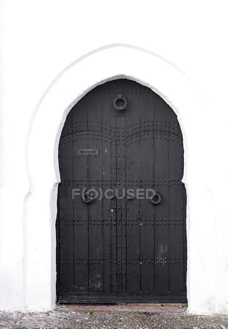 Exterior of white facade with arched doorway — Stock Photo
